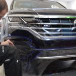 Montage der Schutzfolie an der Frontseite eines VW